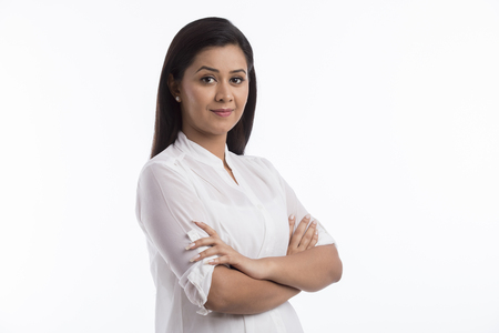Portrait of woman wearing white top standing arms crossed