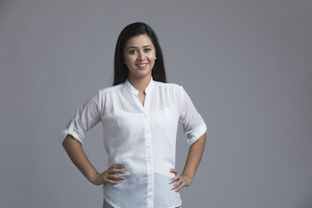 Portrait of smiling woman with hand on hip standing against white background Banco de Imagens