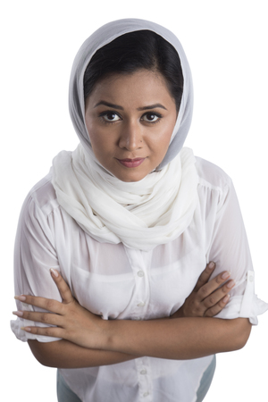 Portrait of woman wearing white head scarf standing arms crossed