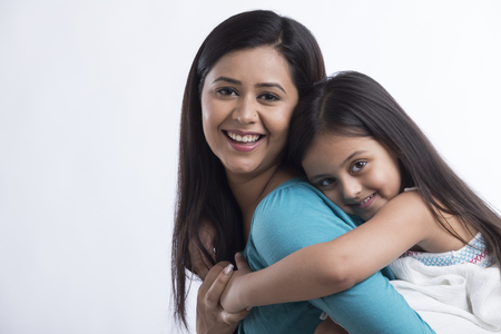 Portrait of mother carrying daughter on back