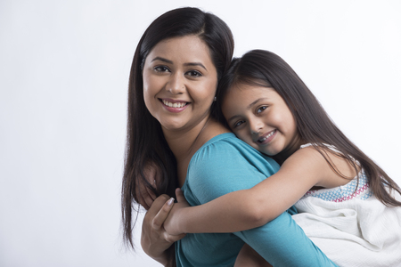 Portrait of mother carrying daughter Stock Photo