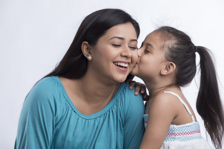 Portrait of daughter kissing mother