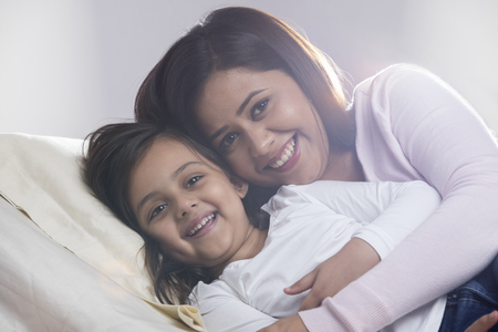 Portrait of smiling daughter and mother sleeping in bed Archivio Fotografico