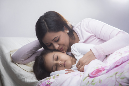 Mother kissing daughter while sleeping in bed Archivio Fotografico