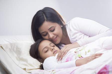 Mother looking at sleeping daughter in bed