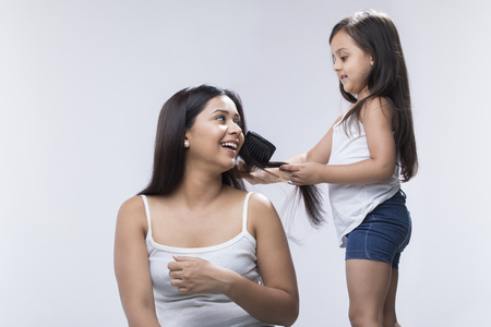 Little girl combing mothers hair