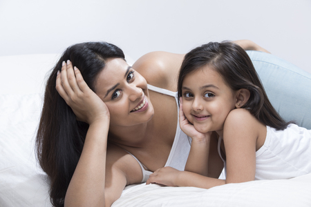 Mother and daughter lying on bed with hand on chin