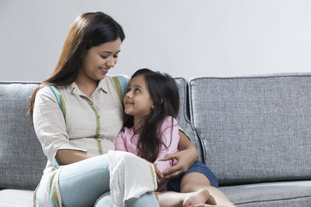 Smiling mother and daughter sitting together on sofa