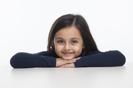 Portrait of little girl leaning on table Banco de Imagens
