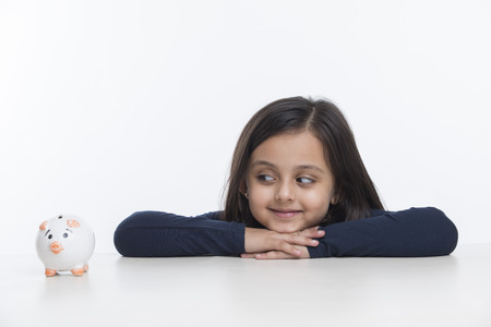 Little girl leaning on table and looking at piggy bank Banco de Imagens
