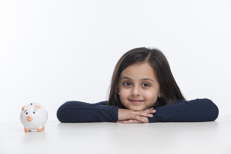 Little girl leaning on table with piggy bank