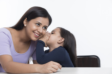 Daughter whispering into mother's ear