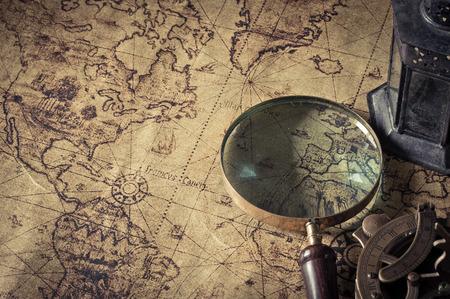 mapa conceptual: Lupa con linterna con brújula en el mapa antiguo, estilo de la vendimia Foto de archivo