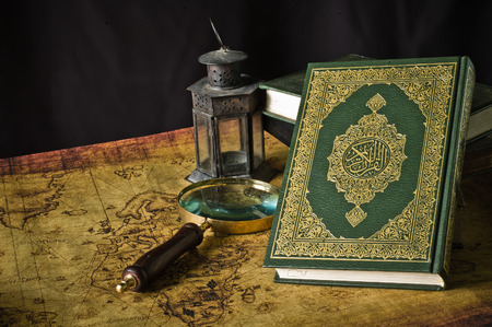 Koran - holy book of Muslims with lantern and compass the old map Stock Photo