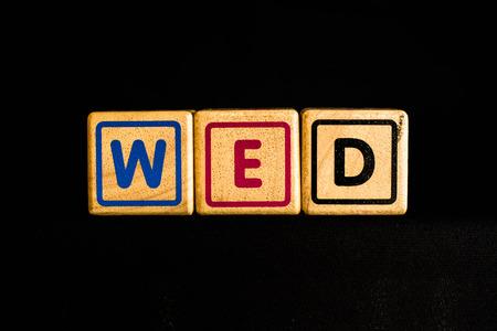 wednesday: Wednesday  on  wood Cubic on black background Stock Photo
