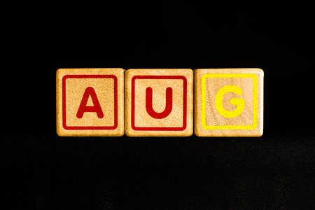 cubic: August  on wood Cubic on black background Stock Photo