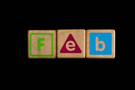 February on wood Cubic on black background photo