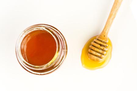 sticky hands: wooden honey dipper on white background