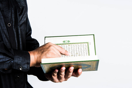 cosiness: Koran in hand ,Quran in hand - holy book of Muslims , on white background