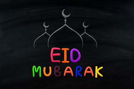 Eid Mubarak, traditional Muslim greeting . On black broad Stock Photo