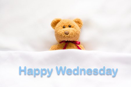 """papel filtro: Oso de peluche acostado en la cama blanca con el mensaje """"Feliz Miércoles"""" Foto de archivo"""