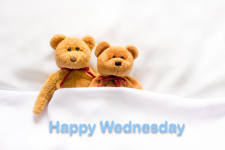 wednesday: Teddy Bear lying in the white bed with message  Happy Wednesday Stock Photo