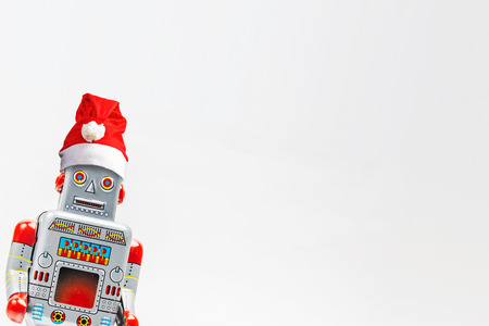 Vintage robot retro classic toy with Christmas hat on white background .