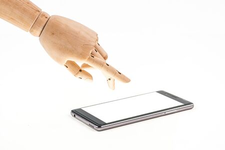 hand of wood doll make fingers to touch with smart phone on white background .