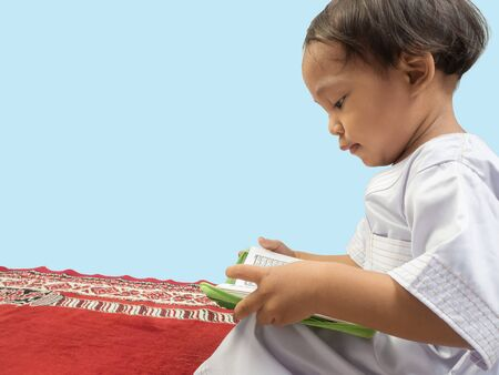 Muslim boy in a dress  reading the Koran , isolate background . Imagens - 128568992