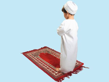 Muslim boy in a dress Praying , isolate background  . Imagens - 128568998