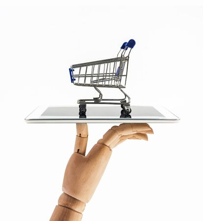 hand of wood doll with shopping cart with tablet on white backgrond , Means shopping online .