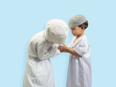 two Muslim boy in a dress Greeting each other, isolate background .