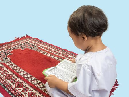 Muslim boy in a dress reading the Koran , isolate background .