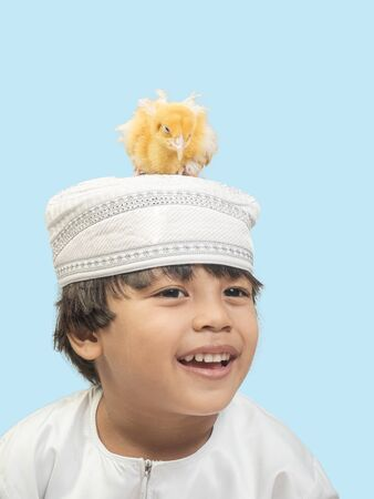 Muslim  boy in a dress and A chick , isolate background .