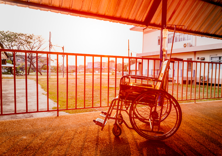 mobility nursing: Vintage wheelchairs use for patient disabled on evening in the hospital Thailand with sunset Stock Photo