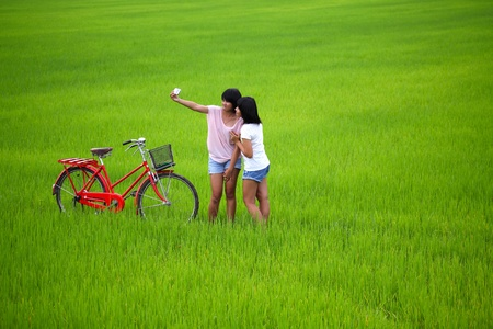 Two girls taking a photo with bike in paddy field photo