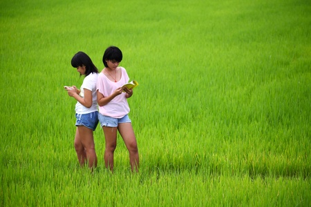 Two young sisters reading a book in paddy field photo
