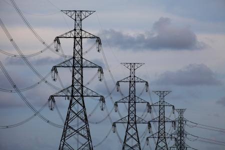 redes electricas: Torres de alta tensi�n sobre fondo de cielo azul Foto de archivo