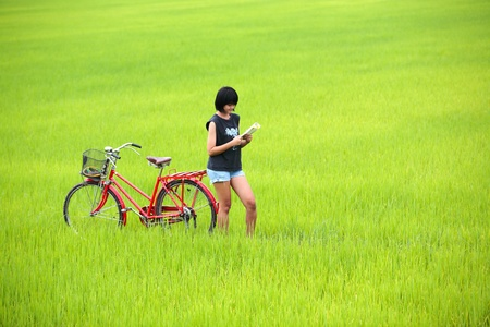 Girl reading a book with bike in paddy field Zdjęcie Seryjne