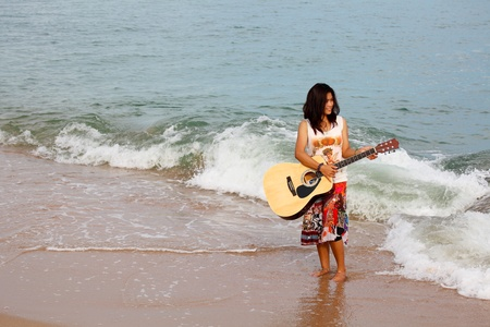 Pretty young woman playing guitar on beach photo