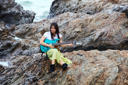 Beautiful asian woman with a guitar on rock photo