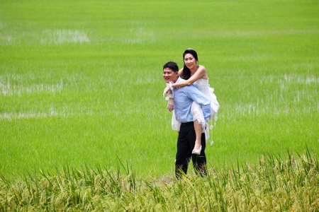 Smiling groom carrying on his back bride in paddy field photo