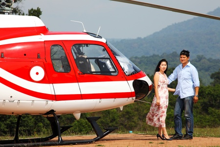 Happy loving couple traveling by helicopter and smiling photo