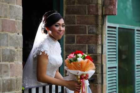 Beautiful bride with bunch of flowers standing on terrace