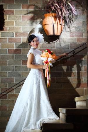 Elegant bride with wedding bouquet over brick wall