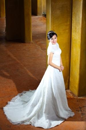 Romantic portrait of the beautiful bride near pillars