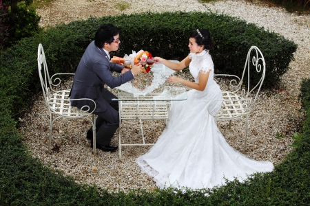 the place is outdoor: Happy couple at the banquet table on field