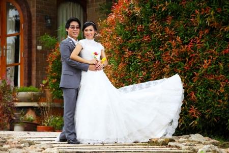 Newly married couple posing in beautiful garden Zdjęcie Seryjne