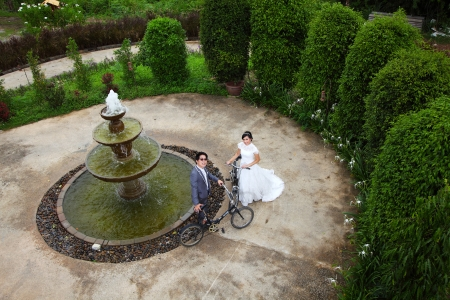 Wedding couple with old bicycles near fountain photo