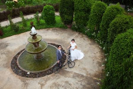 Wedding couple with old bicycles near fountain Zdjęcie Seryjne